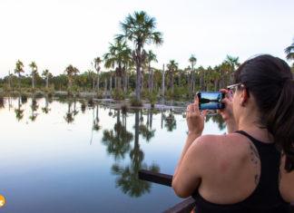 Amanda registrando o pôr do sol na Lagoa das Araras